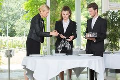 Waiting staff learning how to set table. Set royalty free stock photo