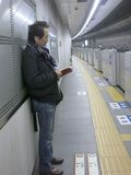 Waiting for the Subway. A man waits for the subway, reading a book, on the metro platform Royalty Free Stock Photo