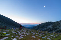 Waiting for the sunrise. Male hiker looking at the majestic view at twilight with half moon in the sky. Location: Italian Alps in Orsiera Regional Park, Piedmont Royalty Free Stock Photo