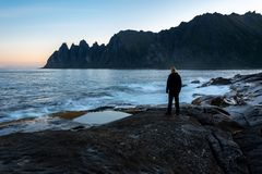 Waiting for sunrise. Man waiting for the sun to rise by the coast of Senja island in northern Norway royalty free stock images