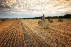 Waiting for sunset... Landscape with a woman in a field full of hay bales before sunset stock photography