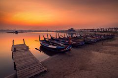 Boats on the Taungthaman Lake at sunrise At Mandalay , Myanmar. Waiting sunset and use wooden bridge be fore ground royalty free stock image