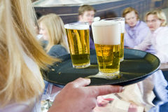 Waiting tables. Waitress bringing a tray with three beers to a group of waiting customers in a restaurant Stock Images