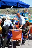 Waiting on tables in Marsaxlokk harbour. Tourists relaxing at a pavement cafes along the waterfront with traditional Maltese fishing boats in the harbour to the Stock Photos