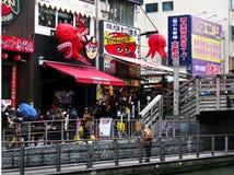 Waiting for takoyaki, Tazaemon Bridge, Dotonbori, Osaka, Japan. Lines of people wait to enter a popular takoyaki octopus ball restaurant near the Tazaemon Bridge Stock Photo