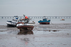 Waiting for the Tide. Boats at Shoeburyness, Essex, England, UK await the rising winter tide in the shadow of Southend Pier Royalty Free Stock Image