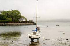 Waiting for the Tide. Small yacht sitting on the beach wating for the tide Royalty Free Stock Images