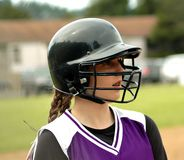 Waiting to Bat. A softball player in batting helmet waiting for her turn at bat Stock Image