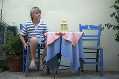 Waiting to be served. Boy waits patiently at a street cafe in Crete to be served Royalty Free Stock Image