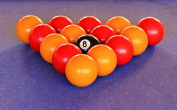 Waiting to Breakout. A  colour image of a triangle of snooker balls surrounding a  8 ball, with a blue felt background Royalty Free Stock Photography