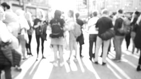 Waiting to cross the street black and white footage. Blur defocused silhouettes of pedestrians people walking in slow motion on Oxford Circus interchange between stock video footage