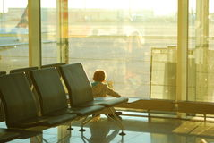 Boy watching airplanes through the window at an airport terminal. A boy waits at the airport for his flight to be called, meanwhile he watches the other Stock Images