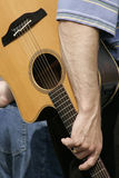 Waiting to Perform. Musician''s hand holding his acoustic guitar Royalty Free Stock Photos
