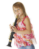Waiting to Play. An attractive young elementary girl standing at the ready with her plastic saxaphone.  On a white background Royalty Free Stock Photo
