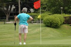 Waiting to putt. Senior woman waiting on putting green Royalty Free Stock Images