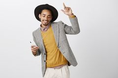 Waiting to sing along with chorus. Good-looking satisfied male model in fashionable clothes and hat, dancing with raised. Index finger, looking down while Royalty Free Stock Photography