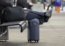 Waiting for a train. Business person waiting for the train with feet on a suitcase at a train station Stock Photography