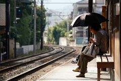 Waiting for the train. A Lady with an umbrella is waiting for a train on the platform of a station near Arashiyama, Kyoto, Japan Royalty Free Stock Images