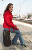 Waiting for a train. Young brunette woman waiting for a train on a railway station royalty free stock photography