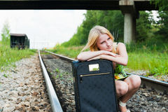 Waiting for a train. Girl leaning on a suitcase waiting for the train Royalty Free Stock Photos