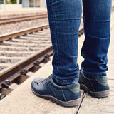 Waiting for the train. Closeup of the feet of a young man wearing jeans who is waiting for the train at the platform of the train station Stock Image