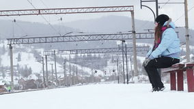 Waiting for train. Girl on bench waiting for train in winter stock video footage