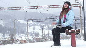 Waiting for train. Girl on bench waiting for train in winter stock footage