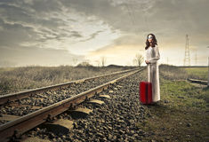 Waiting for the train. Women with suitcase red waiting for the train along the way Royalty Free Stock Images