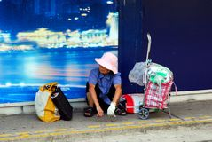 Waiting for the Tram. Elderly woman waiting for a tram with her bags in Hong Kong Royalty Free Stock Photography
