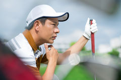 Waiting for the turn. Profile view of a concentrated golf-player sitting and waiting for his turn to play royalty free stock photography