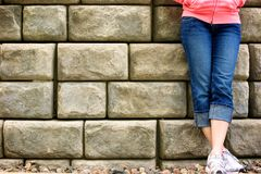 Waiting at the wall. Girl stands beside a wall waiting Royalty Free Stock Photo