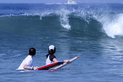 Waiting For The Wave. Two children surfing as they wait to catch a wave as it starts to curl stock photo