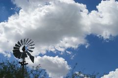 Waiting for the Wind. A Windmill sits silent as summer storm clouds begin to build Stock Photo
