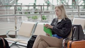 Passenger girl is taking tablet from bag, sitting in waiting room of airport stock video footage