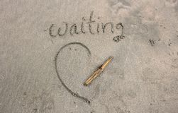 The waiting word on the sand from beach royalty free stock photo