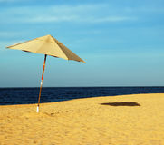 Waiting for You. Beach Umbrella Casting a Shadow on a beach with brilliant blue ocean and sky in the background Stock Image