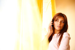 Waiting for you. A beautiful woman waiting at the window while talking on the phone Stock Photos