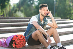 Waiting for you! Handsome serious young man talking on the mobil. E phone while sitting on the staircase with bouquet of roses laying near him Stock Photography