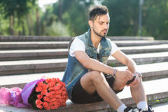 Waiting for you! Handsome serious young man typing message on th. E mobile phone while sitting on the staircase with bouquet of roses laying near him Royalty Free Stock Images