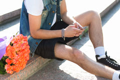 Waiting for you! Handsome serious young man typing message on th. E mobile phone while sitting on the staircase with bouquet of roses laying near him Royalty Free Stock Photos