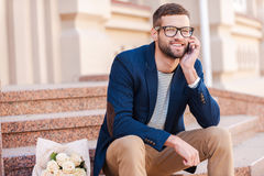 Waiting for you!. Handsome young man in smart jacket talking on the mobile phone and smiling while sitting on the staircase with bouquet of roses laying near him Royalty Free Stock Photo