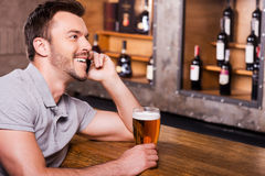 Waiting for you, pal!. Side view of cheerful young man holding glass with beer and talking on the mobile phone while sitting at the bar counter Royalty Free Stock Photos