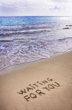 Waiting for you  written in a sandy tropical beach Stock Images
