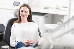 Waiting young woman sitting at dentist room. Portrait of cheerful woman with brilliant smile situating in department of dentist. She leaning back on dental chair Royalty Free Stock Photo