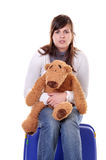 Waiting young woman with teddy bear & suitcase Stock Photo