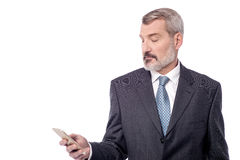 Waiting for your call, focus in phone. Senior businessman looking his mobile phone Royalty Free Stock Photography