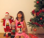 Waitng for real Santa. Girl in pink dress sitting next to Christmas Tree royalty free stock photos