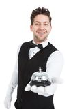 Waitperson Holding Service Bell. Portrait of smiling young waitperson holding service bell over white background Stock Photos