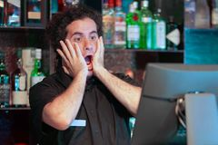 The waitre at the cash register. Male bartender made a mistake in the bill, emotion. A barmaid registrating new order by cash-register. A restaurant worker Stock Photo