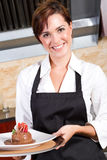 Waitress. Beautiful female waitress presenting plate of dessert Royalty Free Stock Photos